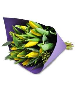 Букет из желтых тюльпанов в фиолетовом бумаги