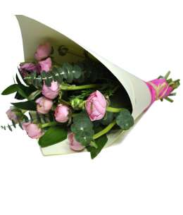 Bouquet of 11 pink ranunculus in white craft paper