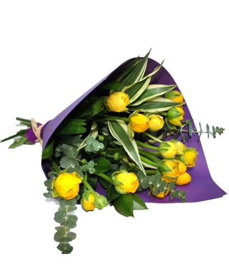 Bouquet of 11 yellow ranunculus in purple craft paper